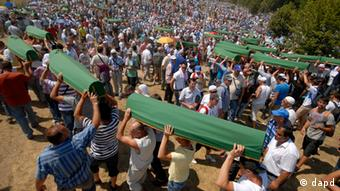 Bosnian Muslim men carry coffins of their relatives during a mass funeral for Srebrenica victims