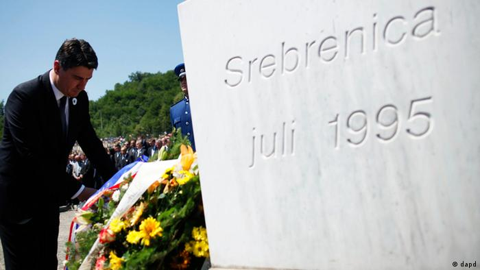 Croatian Prime Minister Zoran Milanovic lays flowers near a memorial plaque at Memorial Center in Potocari during a mass burial, near Srebrenica July 11, 2012. The bodies of 520 recently identified victims of the Srebrenica massacr is buried on July 11, the anniversary of the massacre when Bosnian Serb forces commanded by Ratko Mladic slaughtered 8,000 Muslim men and boys and buried them in mass graves, in Europe's worst massacre since World War Two. REUTERS/Dado Ruvic (BOSNIA - Tags: CONFLICT OBITUARY ANNIVERSARY POLITICS)