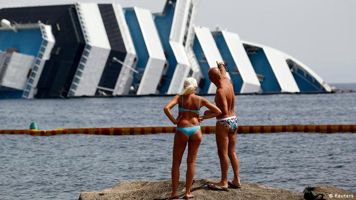Vacationers stands in front of the wreckage of the Costa Concordia