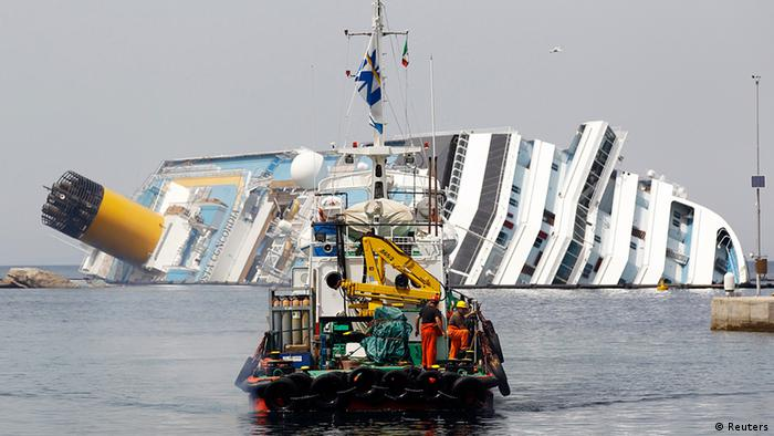 A boat with rescue workers sails in front of capsized cruise liner Costa Concordia near the harbour of Giglio Porto June 20, 2012. Salvage crews began preliminary work this week on preparations to refloat the half-submerged Costa Concordia cruise liner in what is set to be the biggest ever operation of its kind. REUTERS/Max Rossi (ITALY - Tags: DISASTER TRAVEL TRANSPORT)