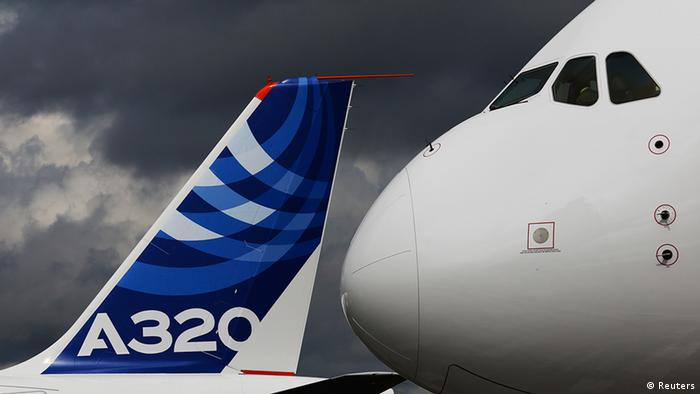 The nose cone of an Airbus A380 overlooks the tail fin of an Airbus A320