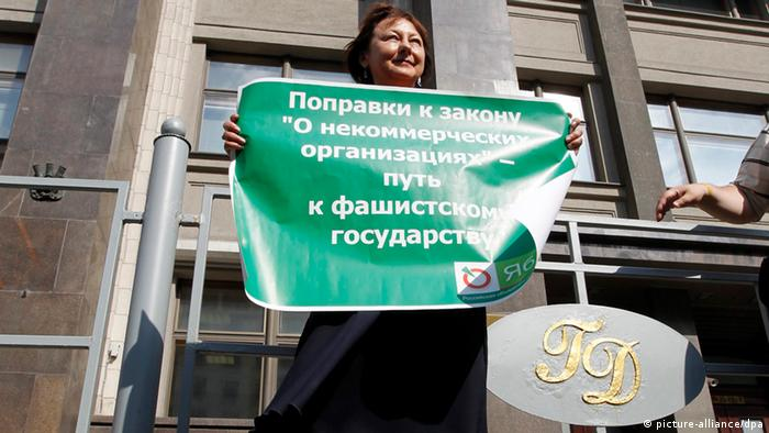 epa03297354 An activist of Yabloko liberal party holds a poster 'The NGO bill will lead to lead to a Fascist State!' outside Russia's lower house of parliament, the State Duma in Moscow, Russia 06July 2012 during an authorized protest against a proposed new bill forcing internationally-funded non-governmental organisations (NGO) to register as 'foreign agents'. EPA/YURI KOCHETKOV +++(c) dpa - Bildfunk+++ pixel