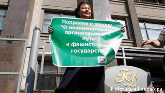 Женщина с плакатом выступает против закона об иностранных агентах