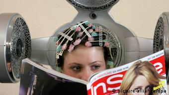 Женщина сушит волосы феном в парикмахерской