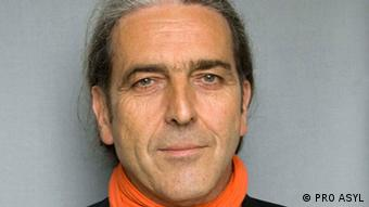 A man with long hair ponytailed behind his head and an orange scarf smiles at the camera (Photo: no data)
