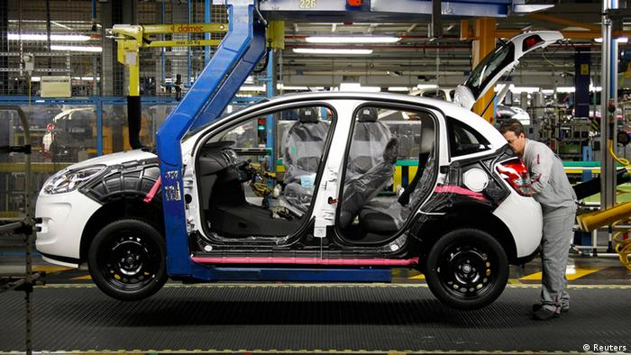 An employee works on the assembly line of the Citroen C3 at the PSA Peugeot Citroen plant in Poissy, near Paris