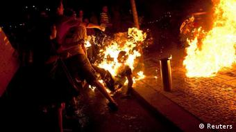 Protesters try to extinguish flames from a protester after he set himself on fire during a demonstration calling for social justice in Tel Aviv July 14, 2012.