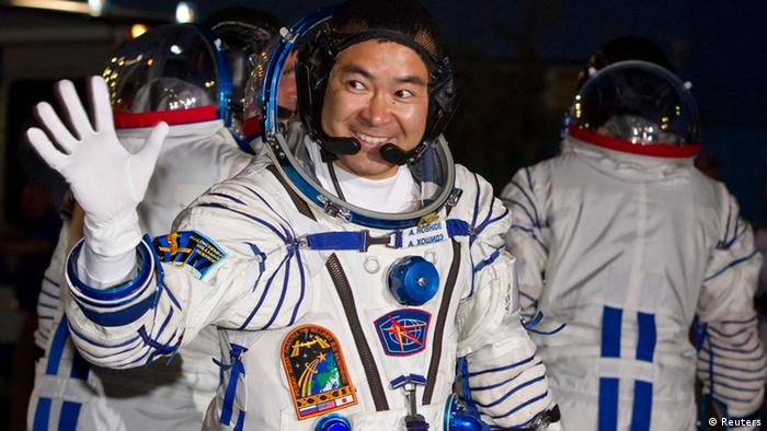 International Space Station (ISS) crew member Japanese astronaut Akihiko Hoshide waves after before the launch of the Soyuz.