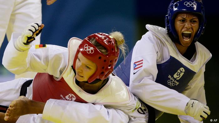 Puerto Rico's Asuncion Ocasio Rodriguez, right, reacts after striking Germany's Helena Fromm during a quarter-final round match for the women's taekwondo
