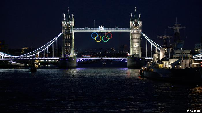The Olympic rings are illuminated while suspended from Tower Bridge, near the HMS Belfast museum warship, as organisers marked one month to go until the London 2012 Olympic Games in London June 27, 2012. The London 2012 Olympics run from July 27 to August 12. REUTERS/Chris Helgren (BRITAIN - Tags: CITYSPACE TRAVEL MILITARY SPORT OLYMPICS)