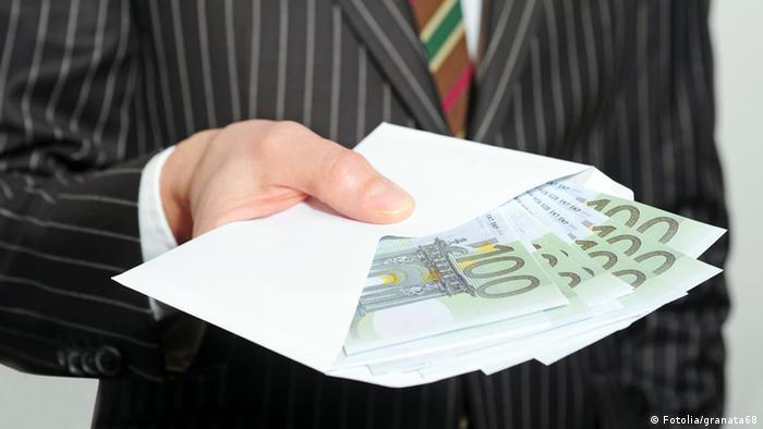Ein Mann hält einen Briefumschlag mit mehreren 100-Euro-Scheinen in der ausgestreckten Hand.