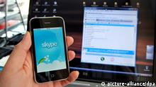 Ein iPhone mit der Software des Internettelefonie-Anbieters Skype ist in Kassel vor einem Laptop zu sehen (Foto vom 11.04.2009). Die Telekom-Mobilfunktochter T-Mobile sperrt in Deutschland den Skype-Zugang auf dem Apple-Handy iPhone. Bei Skype können Nutzeruntereinander kostenlos telefonieren - damit könnten sie also die T- Mobile-Gesprächsgebühren umgehen. Foto: Uwe Zucchi dpa/lhe +++(c) dpa - Report+++