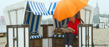 Eine ältere Frau sucht am Samstag (07.07.2012) am Strand der Seebadeanstalt Stralsund im Strandkorb und unter einem Schirm Schutz vor Regen. Laut Angaben der Meteorologen wird das Wetter in der Region in den kommenden Tagen von einem Wechsel aus Sonne und Wolken, teils auch Regen, bestimmt. Foto: Stefan Sauer dpa/lmv