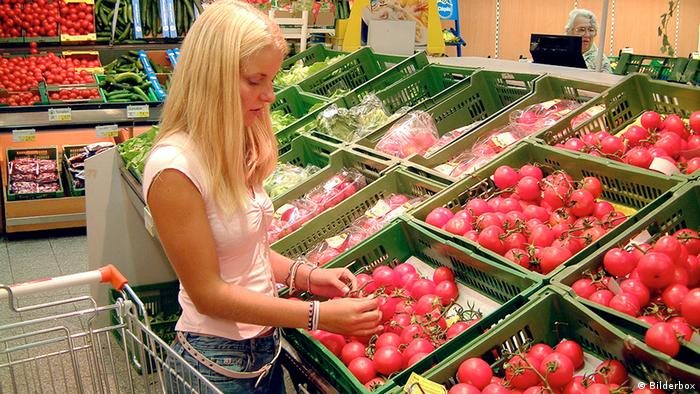 Woman purchasing fruit and vegetables from a supermarket (Photo: dpa/DW)