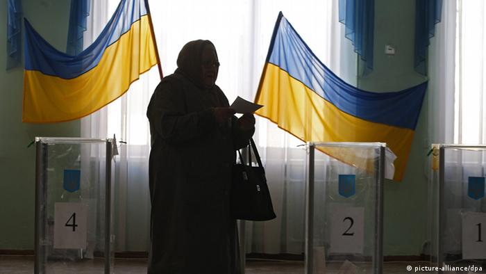 Ukrainian woman pass in front of the voting boxes at a polling station in Kyiv in February 2010
