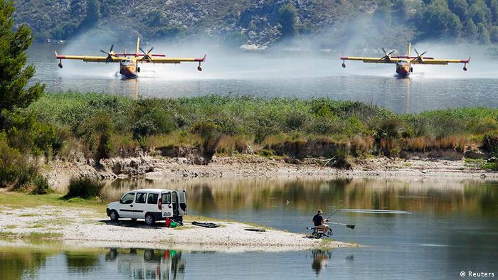 Firefighting planes fetch water from the Beniares reservoir to fight a wildfire next to the Sierra Mariola Nature Park in Cocentaina near Alicante, July 13, 2012. REUTERS/Heino Kalis (SPAIN - Tags: DISASTER ENVIRONMENT TRANSPORT TPX IMAGES OF THE DAY)