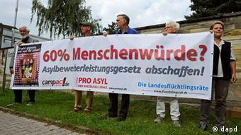 Demonstranten halten ein Plakat. Damit fordern sie die Abschaffung des bisherigen Asylbewerberleistungsgsgesetzes. (Foto: dapd)