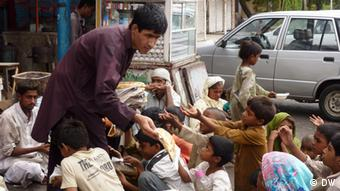 A Pakistani restaurant staffer distributing bread among the poor people