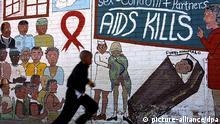 ARCHIV - Ein Schuljunge rennt in Soweto in Johannesburg an einem Wandbild vorbei, das vor Aids warnt (Archivfoto vom 17.05.2002). Am 1. Dezember ist Weltaidstag. Nach Schätzungen des Aidsprogramms der Vereinten Nationen UNAIDS gibt es weltweit 34 Millionen Infizierte, täglich kommen 7400 dazu. In Deutschland leben rund 70 000 Menschen mit HIV. Die Zahl der Neuinfektionen in der Bundesrepublik lag Ende 2010 bei 3000, etwa 550 Infizierte starben. Foto: Kim Ludbrook +++(c) dpa - Bildfunk+++