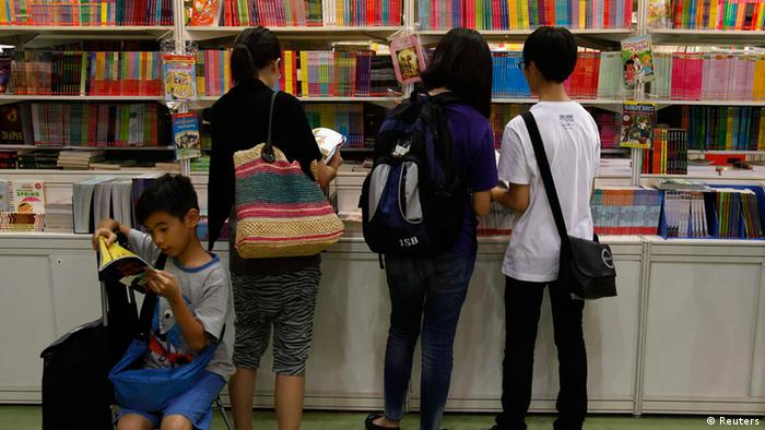 A boy reads beside parents choosing children's books inside the Hong Kong Book Fair July 18, 2012. More than 530 exhibitors from 23 countries and regions took part in the territory's biggest book fair, which opened on Tuesday through July 24. REUTERS/Bobby Yip (CHINA - Tags: MEDIA)