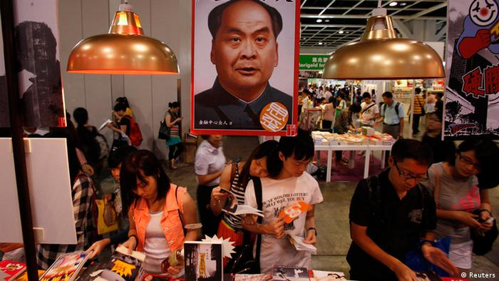 Book lovers read underneath a poster showing the cover of a newly published book Stange Leung Chun-ying, depicting the new Hong Kong Chief Executive as the late Chinese leader Mao Zedong, at the Hong Kong Book Fair July 18, 2012. More than 530 exhibitors from 23 countries and regions took part in the territory's biggest book fair, which opened on Tuesday through July 24. REUTERS/Bobby Yip (CHINA - Tags: MEDIA POLITICS BUSINESS)
