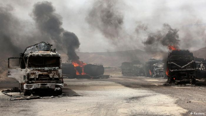 Smoke rises from burning NATO supply trucks in Samangan province, July 18, 2012. A bomb planted by the Taliban destroyed 22 NATO trucks carrying supplies to their forces in northern Afghanistan, the Taliban and police said on Wednesday. REUTERS/ Stringer (AFGHANISTAN - Tags: CIVIL UNREST)