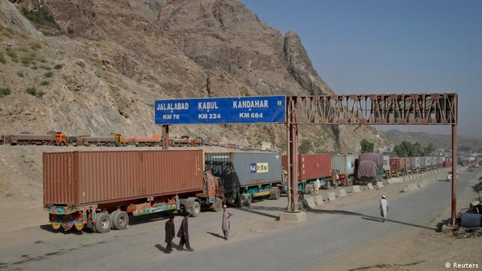 Men walk near a road sign showing the distance to cities in Afghanistan, as trucks drive past in the northwest town of Torkham, at the border crossing to Pakistan, July 4, 2012 (Photo: REUTERS/Shahid Shinwari)