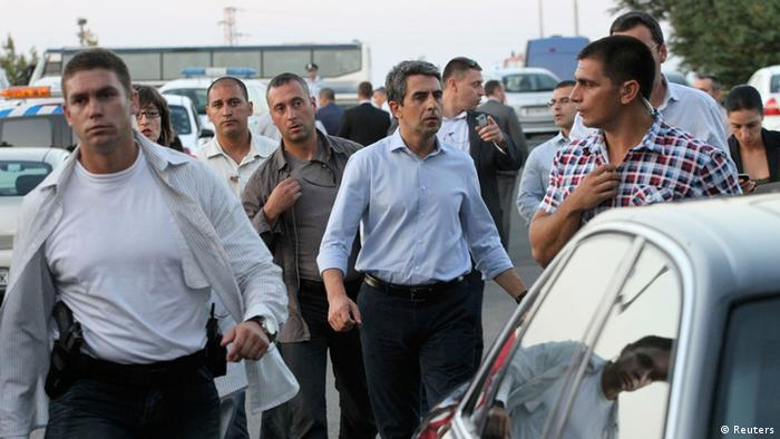 Bulgaria's President Rosen Plevneliev (C) walks near the site of an explosion at Bulgaria's Burgas airport July 18, 2012. At least four people were killed and over 20 injured by an explosion on a bus carrying Israeli tourists outside the airport of the Black Sea city of Burgas on Wednesday. The mayor of the city, on Bulgaria's Black Sea coast, said the bus was carrying Israeli tourists, but the police could not immediately confirm the nationality of the tourists. Police said several other buses at the site had been damaged. REUTERS/Nikolay Doncev (BULGARIA - Tags: DISASTER TRANSPORT POLITICS)