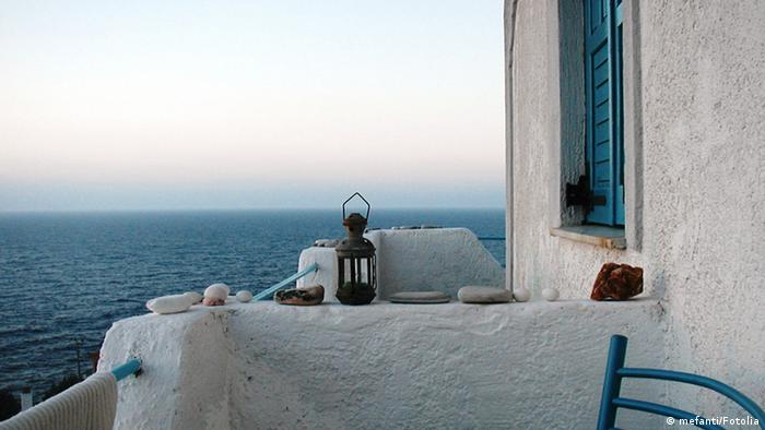 The wall of a Greek house looking out over the blue ocean.