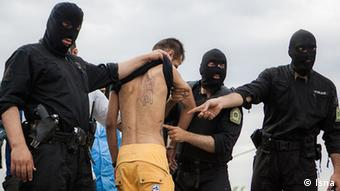 Iranian police wearing black masks and black uniforms pull a man's shirt up to reveal tattoos in a strip-search for indications of drug use (Photo: Isna)