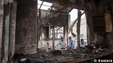 Private security guards stand behind a damaged reception block of Maruti Suzuki's plant in Manesar
