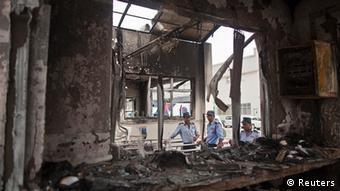 Private security guards stand behind a damaged reception block
