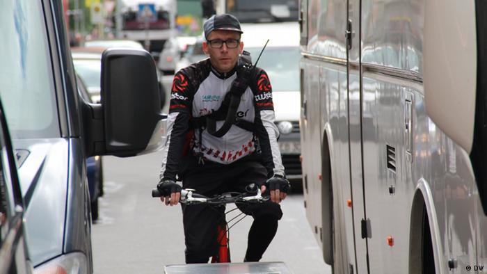 Fahrradkurier zwischen Autos und Bussen