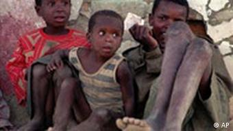 Three African children sitting on a street