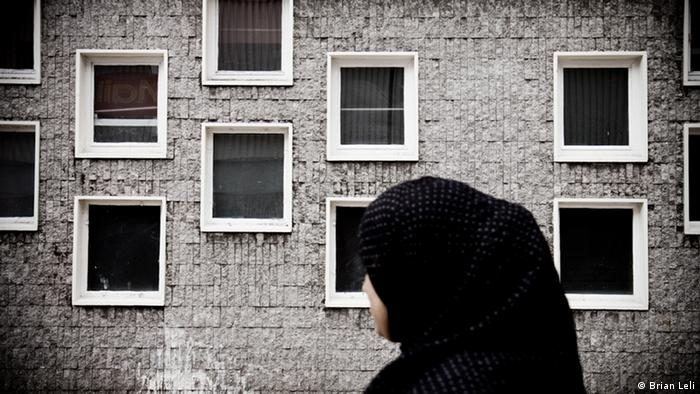 An asylum-seeker wearing a headscarf standing in front of her run-down community home in London