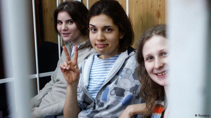 Members of female punk band Pussy Riot, Nadezhda Tolokonnikova (C), Maria Alyokhina (R) and Yekaterina Samutsevich, sit behind bars before a court hearing in Moscow, July 20, 2012. Three members of Pussy Riot were detained on February 21 after they stormed into Moscow's main cathedral to sing a protest song against Vladimir Putin and criticised the Russian Orthodox Church's support for Putin REUTERS/Tatyana Makeyeva (RUSSIA - Tags: POLITICS CRIME LAW)