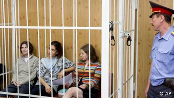 From left, Yekaterina Samutsevich, Nadezhda Tolokonnikova, Maria Alekhina, members of feminist punk group Pussy Riot sit behind bars at a court room in Moscow, Russia, Friday, July 20, 2012. The trial of feminist punk rockers who chanted a punk prayer against President Vladimir Putin from a pulpit inside Russia's largest cathedral started in Moscow on Friday amid controversy over the prank that divided devout believers, Kremlin critics and ordinary Russians. (AP Photo/Misha Japaridze)