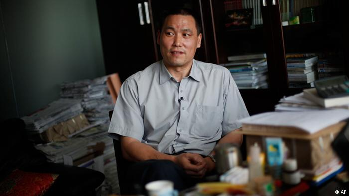 In this photo taken Monday, June 1, 2009, human rights lawyer Pu Zhiqiang, right, speaks to the press, closely watched by plain clothes policemen, not in picture, at his office in Beijing, China. Pu was a law student in 1989 and joined thousands of protesters on Tiananmen Square calling for democracy and changes to China's political system. Pu said he wanted to visit the Martyrs' Monument in Tiananmen Square on the evening of June 3 to honor those killed in the military crackdown on the protests, but he has been detained by police and couldn't get to the monument. (AP Photo/Elizabeth Dalziel)
