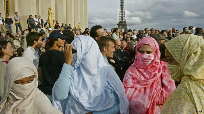 Veiled women take part to a demonstration gathering journalists and members of the Muslim community on the Trocadero Esplanade in Paris, Monday, Aug. 30, 2004, to protest against the detention and ask for the release of French journalists held hostage in Iraq, Christian Chesnot and Georges Malbrunot. France vowed Monday to press ahead with a controversial law banning Islamic head scarves in schools, despite demands by militants holding two French journalists hostage in Iraq. Militants claiming to hold them demanded the law be overturned within 48 hours, a deadline that expires late Monday. The Eiffel Tower is seen behind. (ddp images/AP Photo/Michel Euler)