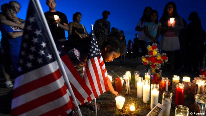 Myia Young, 4, places a candle by an American flag during a vigil for victims behind a theater where a gunman open fire at moviegoers in Aurora, Colorado July 20, 2012. A total of 71 people were shot in Friday's rampage at the Denver-area movie theater that has left 12 people dead, the local police chief said. The suspect, identified by police as James Eagan Holmes, 24, also booby-trapped his Aurora apartment with sophisticated explosives, creating a hazard for law-enforcement and bomb squad officers who swarmed to the scene. REUTERS/ Jeremy Papasso (UNITED STATES - Tags: CRIME LAW)
