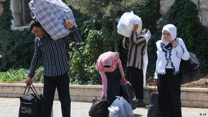 Syrians carry their belongings as they cross into Lebanon at the border crossing point in Masnaa, eastern Lebanon, about 40 kilometers (25 miles) from Damascus, Syria, Friday, July 20, 2012. Private cars as well as taxis and buses carried thousands of people fleeing the violence in the Syrian capital. Syrian troops regained control of a rebellious neighborhood in Damascus Friday as more than 300 people were reported killed the day before in a sharp escalation of the country's civil war. (AP Photo)