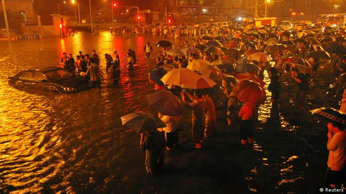 Rescuers and residents stand next to a stranded car which is being pulled up from a flooded street under the Guangqumen overpass amid heavy rainfall in Beijing, July 21, 2012. According to local media, a driver of another submerged car was confirmed dead in hospital after being pulled out critically injured at this street. The heaviest rain in 61 years that lashed Beijing Saturday have left at least four people dead and six others injured, cutting off traffic and also severely disrupted air traffic, Xinhua News Agency reported. REUTERS/Stringer (CHINA - Tags: DISASTER ENVIRONMENT TPX IMAGES OF THE DAY)