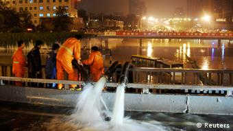 Workers pump flood water as a bus is stranded on a street amid heavy rainfalls in Beijing, July 21, 2012. The heaviest rain storm in six decades to hit the Chinese capital killed at least 10 people and caused widespread chaos, flooding streets and stranding 80,000 people at the city's main airport, state media reported on Sunday. Picture taken July 21, 2012. REUTERS/Stringer (CHINA - Tags: ENVIRONMENT DISASTER TRANSPORT) CHINA OUT. NO COMMERCIAL OR EDITORIAL SALES IN CHINA