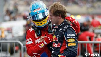 Second placed Red Bull Formula One driver Sebastian Vettel (R) of Germany is congratulated by winner Ferrari Formula One driver Fernando Alonso of Spain after the German F1 Grand Prix at the Hockenheimring in Hockenheim July 22, 2012. REUTERS/Alex Domanski (GERMANY - Tags: SPORT MOTORSPORT F1)