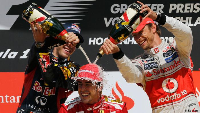 Ferrari Formula One driver Fernando Alonso of Spain is doused in champagne by second placed Red Bull driver Sebastian Vettel of Germany (L) and third placed McLaren Mercedes driver Jenson Button of Britain (R) after winning the German F1 Grand Prix at the Hockenheimring in Hockenheim July 22, 2012. REUTERS/Wolfgang Rattay (GERMANY - Tags: SPORT MOTORSPORT F1 TPX IMAGES OF THE DAY)