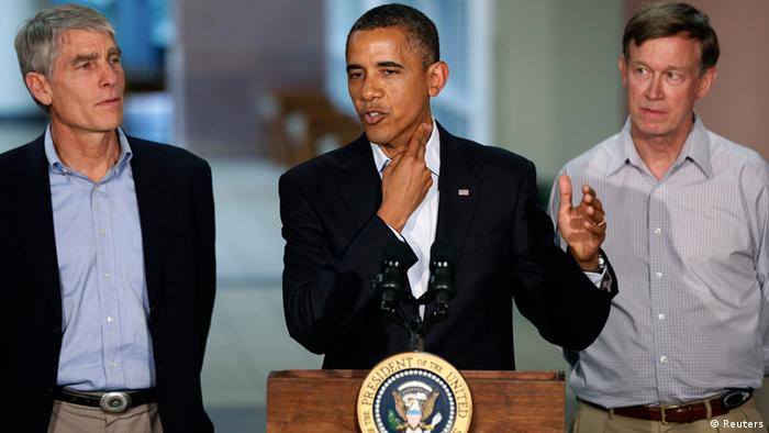 U.S. President Barack Obama (C) demonstrates a story of survival while speaking at the University of Colorado Hospital after he met with families bereaved after a gunman went on a shooting rampage at a movie theater in Aurora, Colorado July 22, 2012. Standing beside Obama are U.S. Senator Mark Udall (L) and Colorado Governor John Hickenlooper (R). Obama headed to Aurora, Colorado, on Sunday to meet families grieving their losses Friday's mass shooting that has stunned the nation and rekindled debate about guns and violence in America. REUTERS/Larry Downing (UNITED STATES - Tags: POLITICS CRIME LAW TPX IMAGES OF THE DAY)