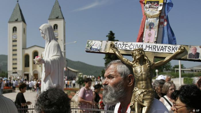 Pilgrims walks around the statue of Blessed Virgin Marry near the St James' Church at Medjugorje, Bosnia and Herzegovina, some 120 kilometers (75 miles) south of the Bosnian capital of Sarajevo on Sunday, June 25, 2006. Thousands of Christian pilgrims gathered in this southern Bosnian village, joining the six people who as youths 25 years ago said they began seeing visions of the Virgin Mary. The Medjugorje apparition has been disputed for years. Unlike Fatima in Portugal or Lourdes in France, the Roman Catholic church is cautious about calling the sightings authentic, and has not formally approved Medjugorje as a shrine site.(ddp images/AP Photo/Amel Emric)