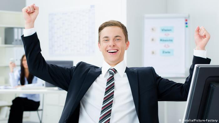 Улыбающийся молодой человек поднял руки в победоносном жесте.
