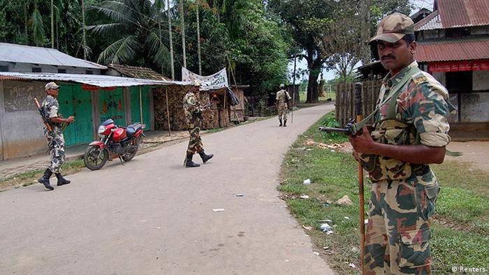 Indian security personnel patrol on a street during curfew near Kokorajhar town in the northeastern Indian state of Assam