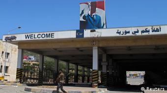A Free Syrian Army member walks past a a torn picture of Syrian President Bashar Assad at Syrian border crossing